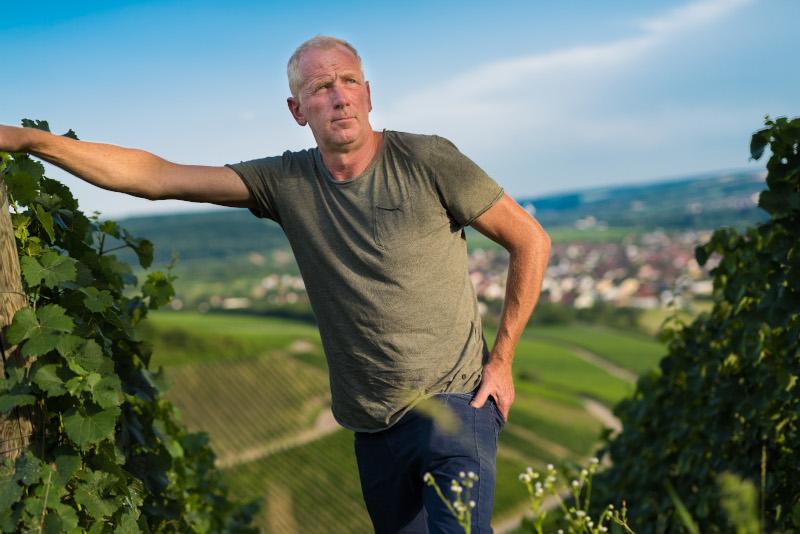 echt fränkische. Die Winzer aus Franken mit einem Glas Wein und Blick auf die Weinberge